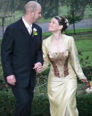 This colourful bride has a boned strapless bodice panelled with burgundy and gold brocades, featuring a burgundy ribbon between the gold loops. Her Aline skirt is a raw silk lookalike shantung satin. She wears in addition a 'shrug style' jacket with long sleeves, in the same gold fabric as the skirt.