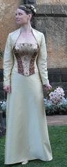 This colourful bride has a strapless boned bodice panelled with burgundy and brocades, featuring a burgundy ribbon between the gold loops. Her A line skirt is a raw silk lookalike shantung satin. She wears in addition a 'shrug style' jacket with long sleeves, in the same gold fabric as the skirt.
